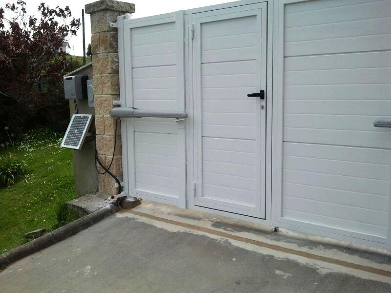 Puerta batiente 2 hoja con puerta peatonal incorporada en panel sandwich acan. blanco automatizado sistema solemyo